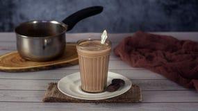 在一块玻璃的热的可可粉饮料巧克力牛奶木表面上 免版税库存图片