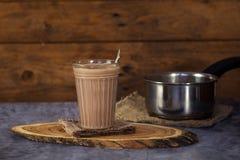 在一块玻璃的热的可可粉饮料巧克力牛奶木表面上 免版税库存照片