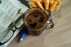 在一块玻璃的热的咖啡一个早晨好和早报 免版税库存照片