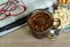 在一块玻璃的热的咖啡一个早晨好和早报 图库摄影