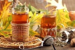 在一块玻璃的热的绿茶在木背景 库存照片