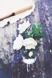 在一块玻璃的狂放的玫瑰束在夏天庭院桌上 免版税库存图片