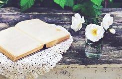 在一块玻璃的狂放的玫瑰色花在生锈的木桌上 免版税库存图片