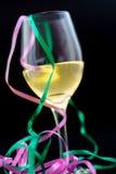 在一块玻璃的白葡萄酒与丝带和黑背景 库存图片