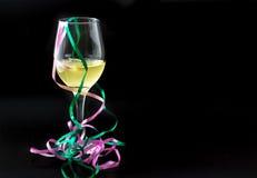 在一块玻璃的白葡萄酒与丝带 免版税库存图片
