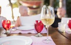 在一块玻璃的白葡萄酒在一家餐馆的表上我的 库存图片