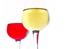 在一块玻璃的白葡萄酒在红葡萄酒背景 免版税库存照片