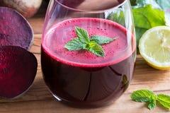 在一块玻璃的红色甜菜汁与柠檬和甜菜绿叶 免版税库存照片