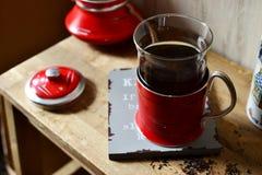 在一块玻璃的红茶在一个红色玻璃持有人 免版税库存图片