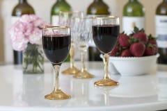 在一块玻璃的红葡萄酒在白色桌背景 免版税库存照片