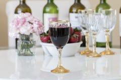 在一块玻璃的红葡萄酒在白色桌背景 免版税库存图片