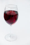 在一块玻璃的红葡萄酒在白色背景-现实照片图象 免版税库存照片