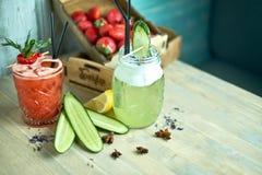 在一块玻璃的自创黄瓜和薄菏柠檬水在蓝色木背景 JPG 库存照片