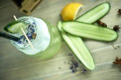 在一块玻璃的自创黄瓜和薄菏柠檬水在蓝色木背景 JPG 免版税图库摄影