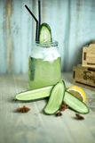 在一块玻璃的自创黄瓜和薄菏柠檬水在蓝色木背景 JPG 库存图片