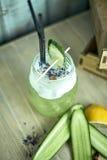 在一块玻璃的自创黄瓜和薄菏柠檬水在蓝色木背景 JPG 免版税库存照片