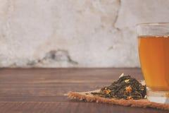 在一块玻璃的自然绿茶在木棕色桌上 免版税库存图片