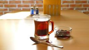 在一块玻璃的茶在砖背景 免版税库存照片