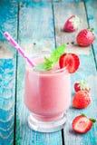 在一块玻璃的草莓圆滑的人与秸杆 免版税图库摄影