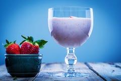 在一块玻璃的草莓圆滑的人用在旁边碗的新鲜的草莓 免版税库存照片