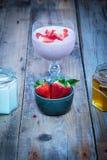 在一块玻璃的草莓圆滑的人用新鲜的草莓、蜂蜜和酸奶 免版税库存照片