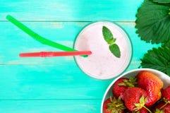 在一块玻璃的草莓奶昔在莓果和绿色叶子中的明亮的背景 库存照片