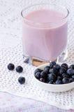 在一块玻璃的蓝莓酸奶与匙子和蓝莓 免版税库存图片