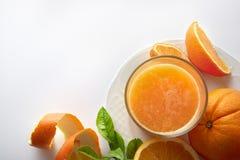 在一块玻璃的被紧压的橙汁在板材顶视图 免版税图库摄影