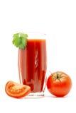 在一块玻璃的西红柿汁与在白色有蕃茄近的绿色叶子隔绝的 库存图片