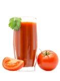 在一块玻璃的西红柿汁与在白色有蕃茄近的绿色叶子隔绝的 库存照片
