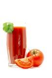 在一块玻璃的西红柿汁与在白色有蕃茄近的绿色叶子隔绝的 免版税库存照片