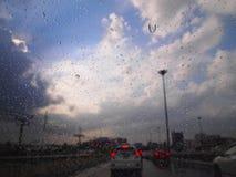 在一块玻璃的雨珠与红绿灯和美丽的blured蓝天和云彩在背景中 库存图片