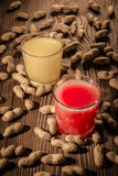 在一块玻璃的香蕉和草莓汁在与坚果1的木背景 免版税库存图片