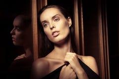 在一块玻璃附近的美丽的少妇在内部 库存照片