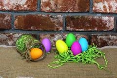 在一块绿皮书巢和玻璃的五颜六色的复活节彩蛋在红色老砖背景刺激 免版税图库摄影