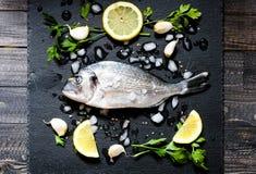 在一块黑石头的鲜鱼Orata与菜 免版税库存图片