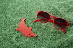 在一块绿色毛巾的太阳镜 免版税图库摄影