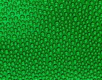 在一块绿色玻璃(抽象背景)的水下落 免版税库存图片
