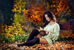 读在一处浪漫秋天风景的年轻白种人肉欲的妇女一本书。相当女孩画象在秋季森林里 图库摄影
