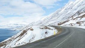 在一大多雪mountian附近的弯曲的路标题 免版税图库摄影