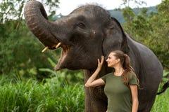 在一头大象附近的女孩身分在密林 库存照片