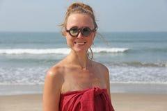 在一头红色礼服和金发的美丽的女孩畸形人,在海的背景 圆的木玻璃的夏天女孩 异常 图库摄影