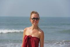 在一头红色礼服和金发的美丽的女孩畸形人,在海的背景 圆的木玻璃的夏天女孩 异常 免版税库存照片