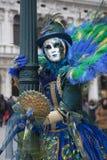 在一套五颜六色的蓝绿色和黄色孔雀狂欢节服装和面具威尼斯的威尼斯式狂欢节字符 免版税库存照片