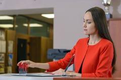 在一套明亮的红色西装的一个母上司投入封印对合同在接待室 免版税库存图片