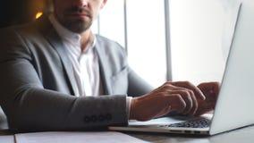 在一套灰色衣服的时髦的年轻商人键入在膝上型计算机的 影视素材