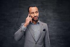 在一套灰色衣服的时髦的有胡子的黑男性在巧妙的电话谈话 免版税库存图片