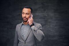 在一套灰色衣服的时髦的有胡子的黑男性在巧妙的电话谈话 免版税库存照片