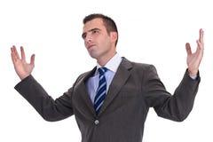 在一套灰色衣服的年轻商人用被举的手,看 库存图片