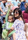 在一套神仙的服装打扮的普珥节节日的一个年轻访客坐在她的妈妈` s手在凯瑟里雅,以色列 免版税库存图片